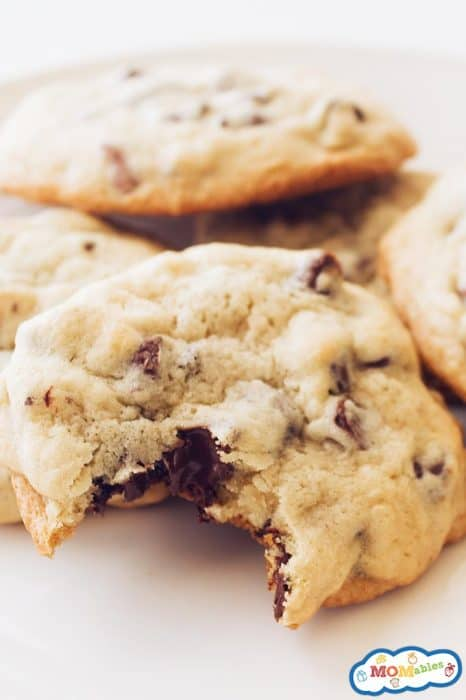 image: pile of chocolate chip cookies on a plate, one of them has a bite taken out of it.