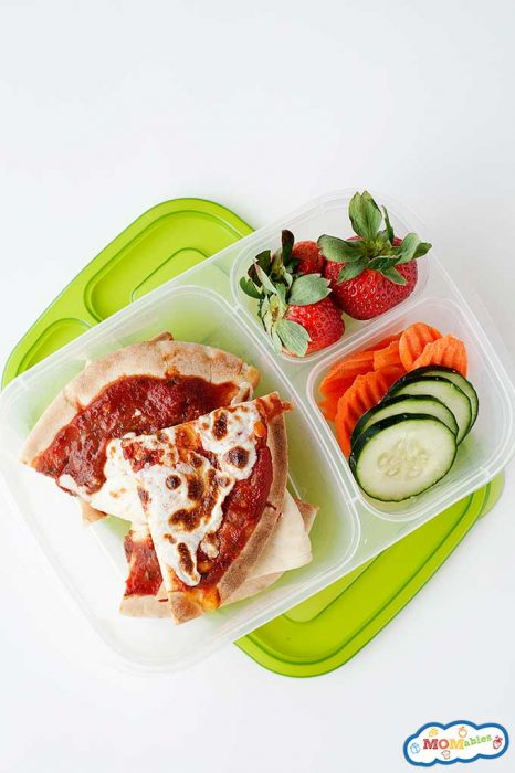 sliced pita pizza in a lunch container with strawberries, cucumber, and carrots.