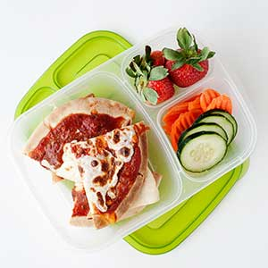 a lunch container filled with a sliced pizza, cucumber, carrots, and strawberries.