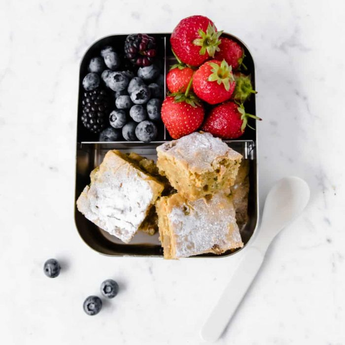 small snack tin with carrot zucchini cake bars, and berries inside