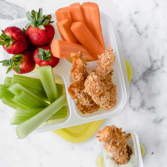 fish sticks in a lunch container with celery sticks and strawberries