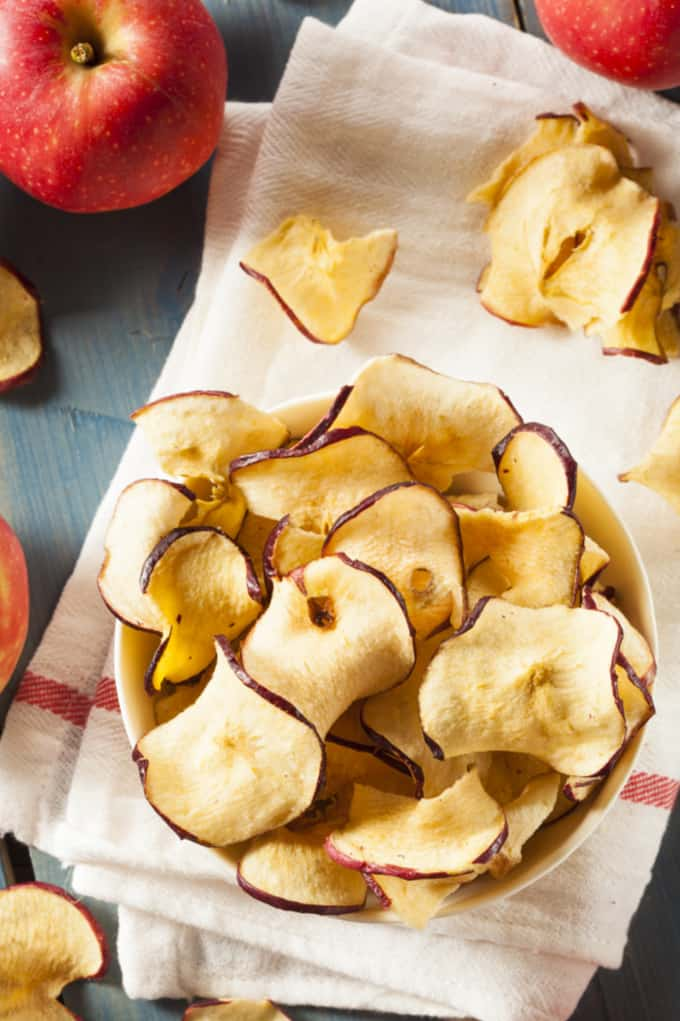 image: small bowl of curly apple chips, next to a few fresh apples