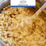 Image: Macaroni & cheese in a pot being stirred with a spoon.