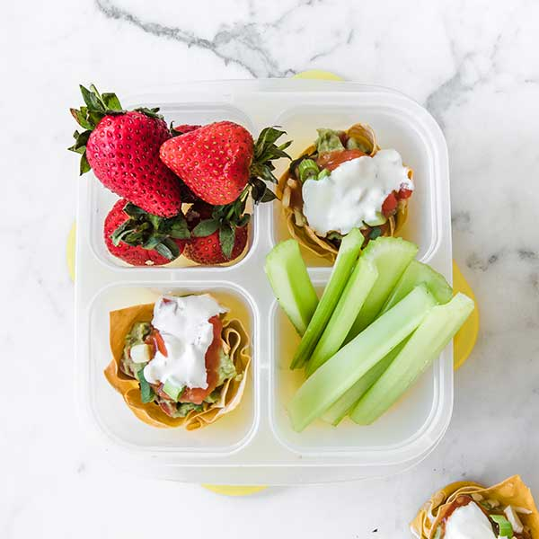 a lunch container filled with taco cups, strawberries, and celery sticks