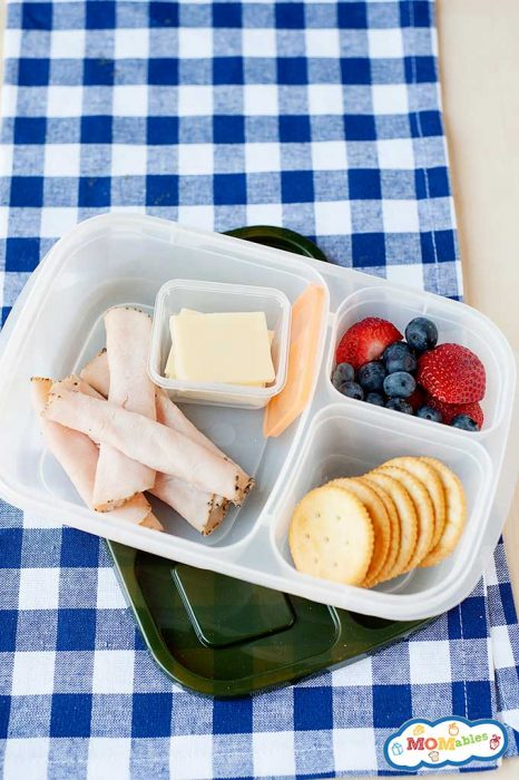 a lunch container filled with rolled deli turkey, sliced cheese, crackers, blueberries, and strawberries.