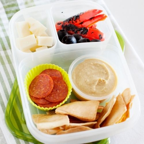 a lunch container filled with pita chips, sliced pepperoni, hummus, cheese cubes, and roasted red bell pepper.