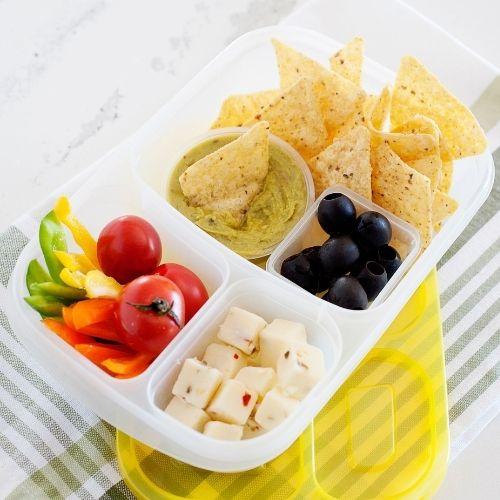 a lunch container filled with tortilla chips, guacamole, grape tomatoes, sliced bell pepper, cheese cubes, and black olives.