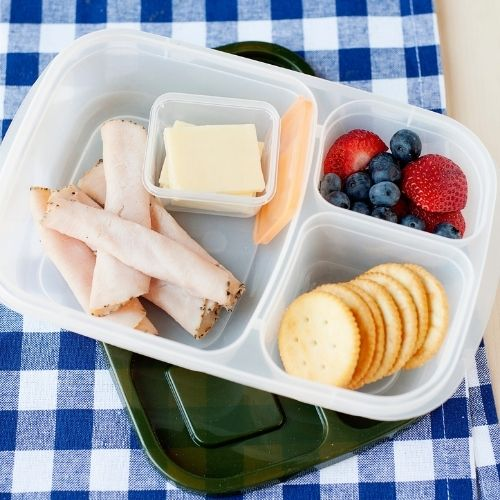a lunch container filled with rolled deli turkey, crackers, silced cheese, and berries