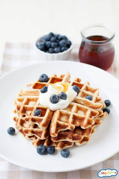 Image: gluten free waffles stacked on a white plate and topped with syrup, whipped topping, and blueberries.