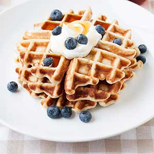 image: stack of waffles on a plate topped with bluberries and cream.