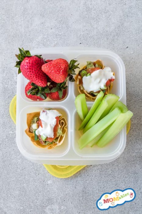 2 taco cups topped with sour cream and guacamole in a lunch container with celery sticks and strawberries.