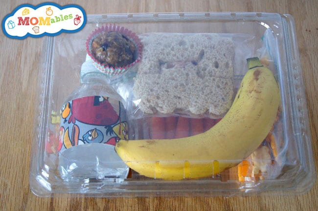 Image: a sandwich, mini water bottle, banana, and treat packed into a clear, plastic box.