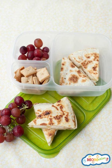 apple and cheese quesadilla triangles in a lunch container with purple grapes and cheese crackers