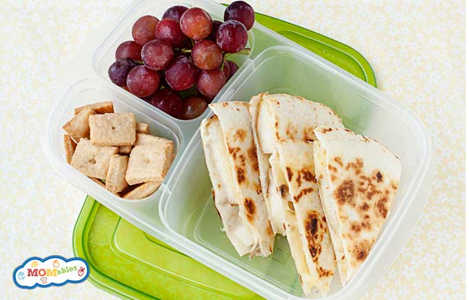 closeup overhead view of four quesadilla triangles in a lunch container with grapes and cheese crackers