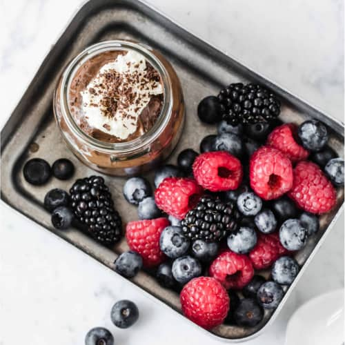a cup of chocolate pudding topped with whipped cream and served with fresh berries.