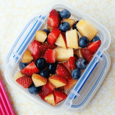 small plastic container with fruit and lemonade inside.