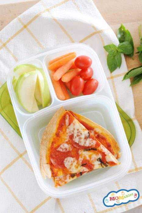 image: slices of tortilla pizza in a lunch container with sliced apples, carrots and tomatoes.