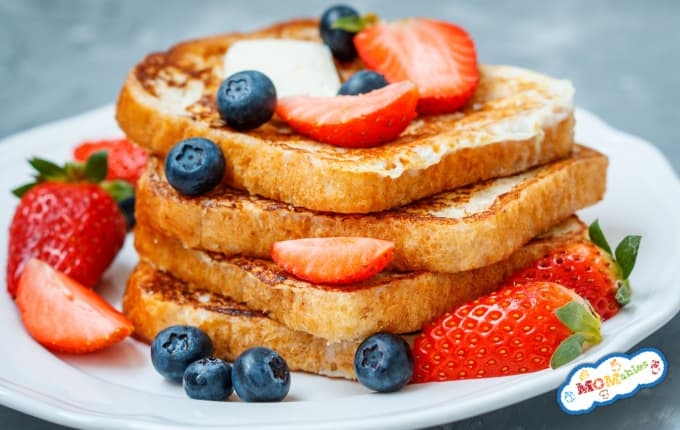 image: stack of four french toast slices toped with strawberries and blueberries