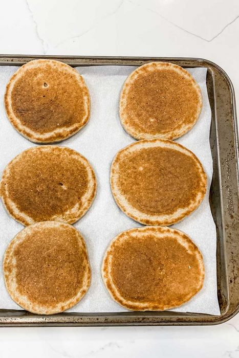 pancakes on a baking sheet in rows for freezing