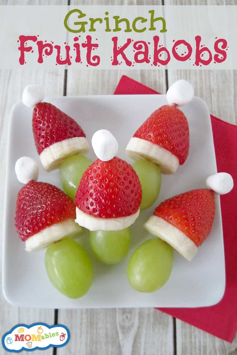 Fruit kabobs with green grapes, sliced banana, a strawberry, and topped with a mini marshmallow.