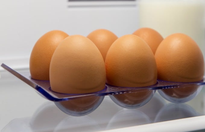 image: six brown eggs in a fridge