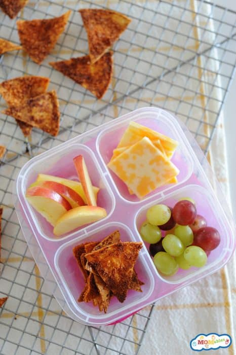 Image: homemade doritos in a snack box with sliced apple, grapes, and cheese.