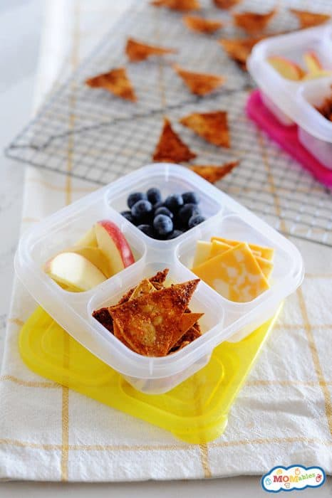 Image: homemade doritos in a snack box with sliced apple, blueberries, and cheese.