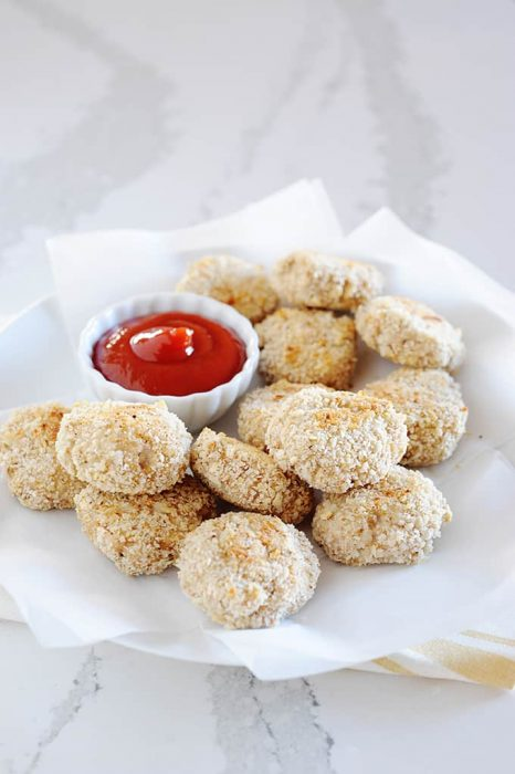 homemade chicken nuggets on a plate with small dish of ketchup