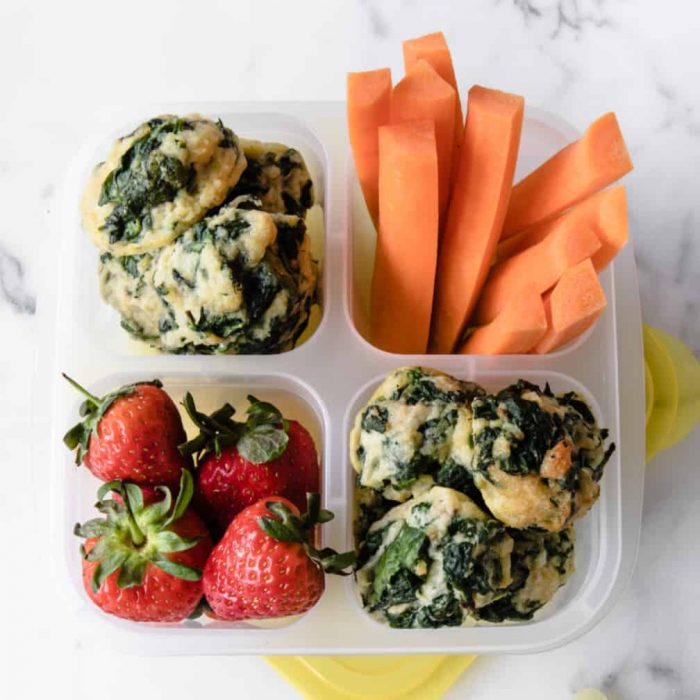 Parmesan Spinach Balls in a small lunch container with carrot sticks and strawberries