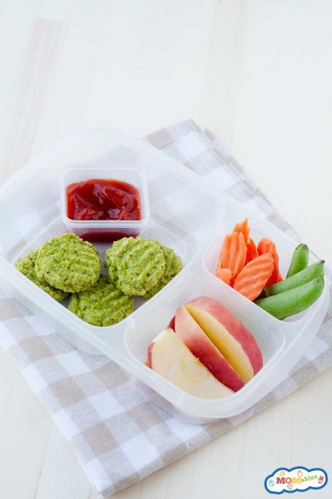 A lunch container with broccoli nuggets and a sauce container of ketchup. Sliced apples and sugar snap peas in the side compartments.