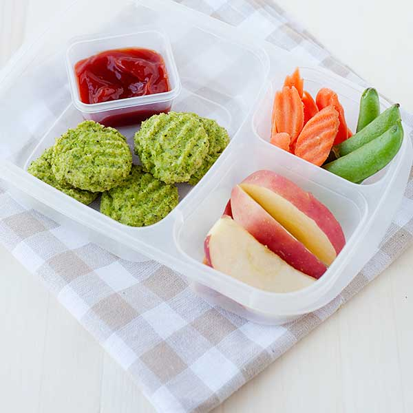 broccoli nuggets in a lunch container with a sauce container or ketchup and sliced apples, sugar snap peas, and sliced carrots on the side.