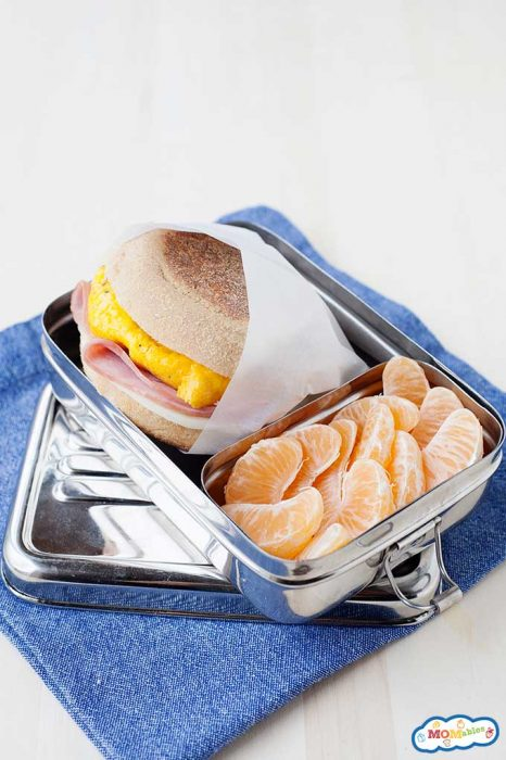homemade egg mcmuffin with egg, ham, and cheese wrapped in wax paper and packed in a tin lunchbox with mandarin orange segments.
