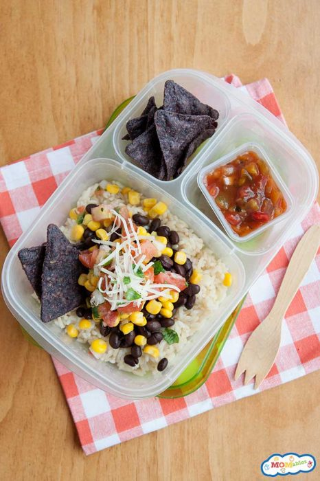 A burrito bowl in a lunchbox made with rice, black beans, corn, cheese, and pico de gallo. Blue corn tortilla chips in the side compartment with salsa in a mini sauce container.