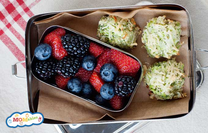 three broccoli tots in a small lunch container with berries