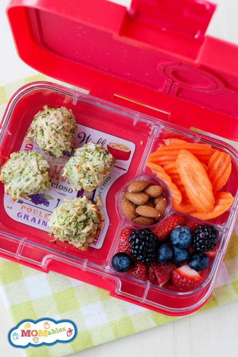 broccoli tater tots in a pink lunch container with fruit, sliced carrots and almonds