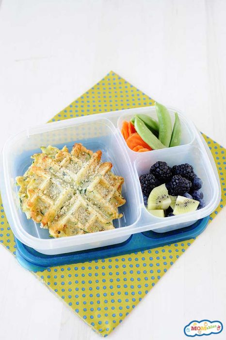 Parmesan zucchini waffles in a plastic lunch container with blackberries, kiwi, and veggies.