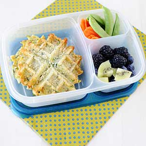 zucchini parmesan waffle in a lunch container with blackberries, cubed kiwi, sugar snap peas, and sliced carrots.