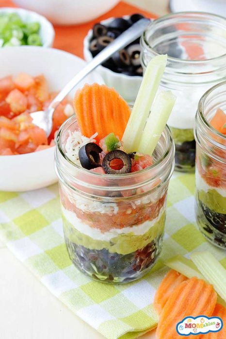 black beans, guacamole, salsa, tomatoes, cheese, and black olives layered into a glass jar and served with fresh vegetables