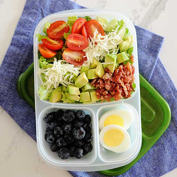 a salad topped with bacon, avocado, tomatoes, and cheese in a lunch container with blueberries. and a hard-boiled egg.