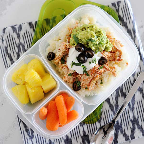 rice topped with shredded chicken, guacamole, sour cream, and sliced black olives in a lunch container with baby carrots and pineapple.