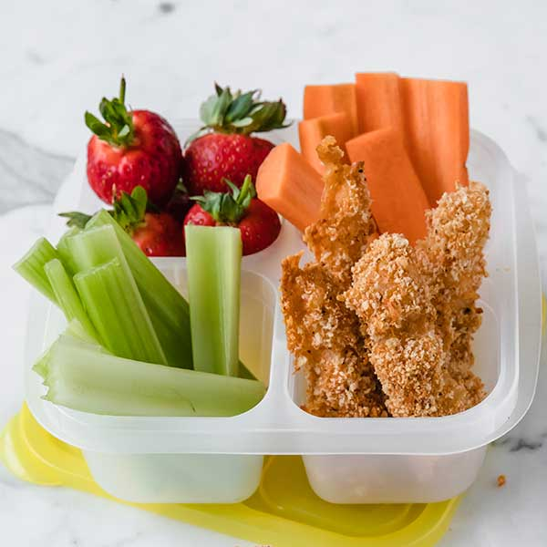 a lunch container with fish sticks, carrot sticks, celery, and fresh strawberries.