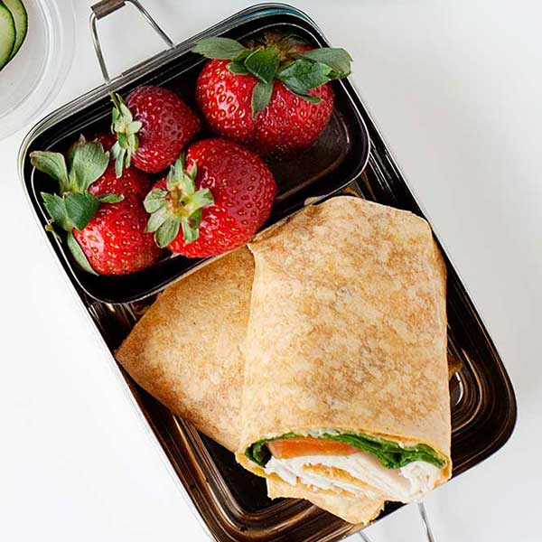 a turkey and vegetables wrap in a metal lunch container with fresh strawberries.