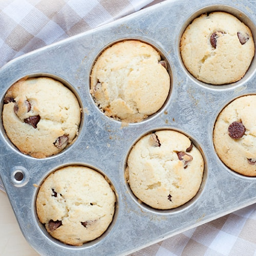 image: six chocolate chip pancake muffins in a silver muffin pan.