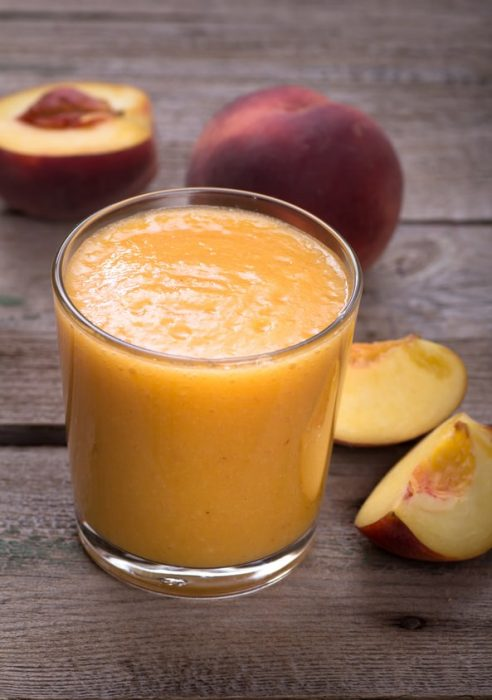 mango peach smoothie in a glass cup