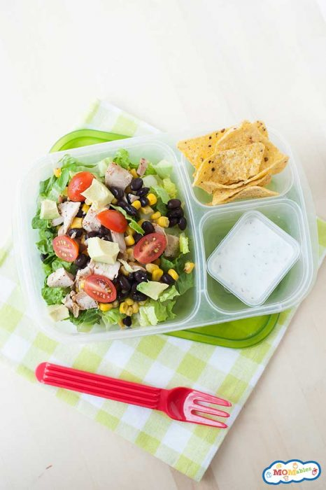 a bed of lettuce in a lunchbox and  topped with corn, black beans, grilled chicken, and tomatoes. On the side are chips and a sauce container filled with ranch dressing.