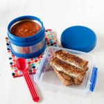 Image: grilled cheese slices in a lunch container with tomato soup in a thermos on the side.