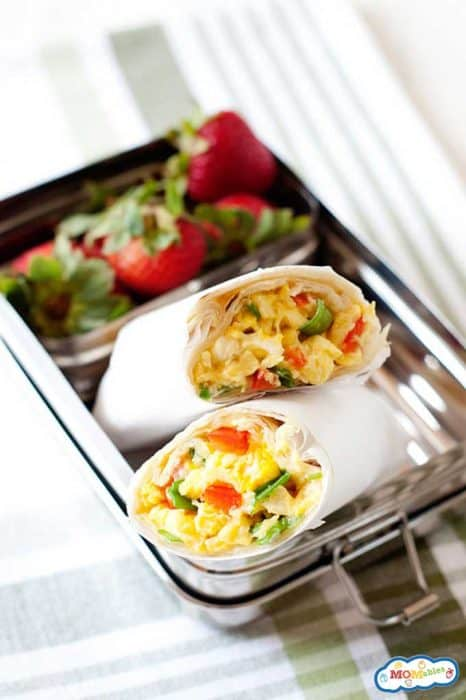Breakfast burritos wrapped in parchment in a lunchbox with fresh berries.