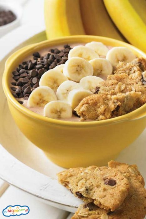 a peanut butter cup smoothie bowl topped with sliced bananas, chocolate chips, and cookie crumble.