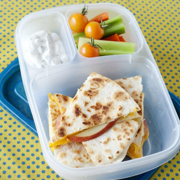 cheese quesadilla with apple slices, dip and vegetables in a lunchbox