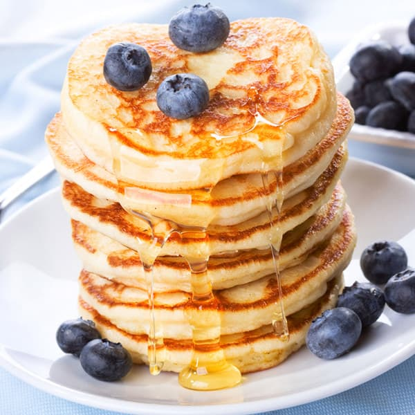 image: stack of pancakes dripping with syrup and topped with blueberries
